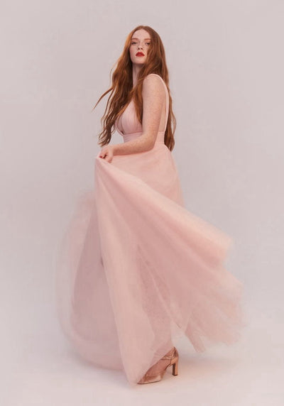 Woman in pale pink tulle dress side.