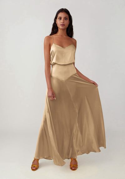 Woman in soft gold blouson top full skirt dress front.