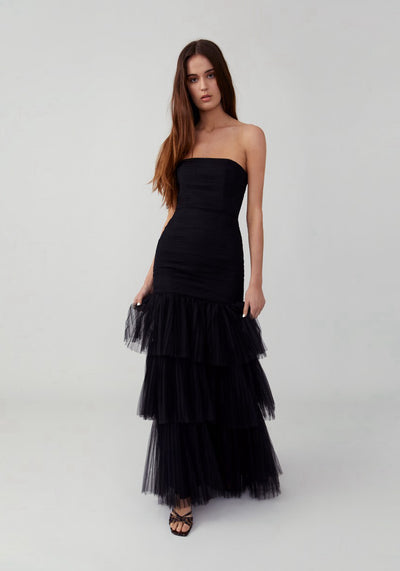 Woman in black strapless tiered dress front.