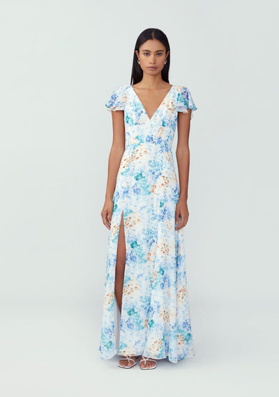 Woman in white floral v neck sleeved maxi dress front.