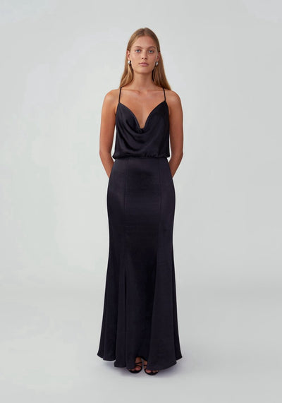 Woman in black flared maxi dress front.