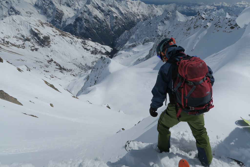 Rider dropping into a line while backcountry splitboarding in the Italian Alps