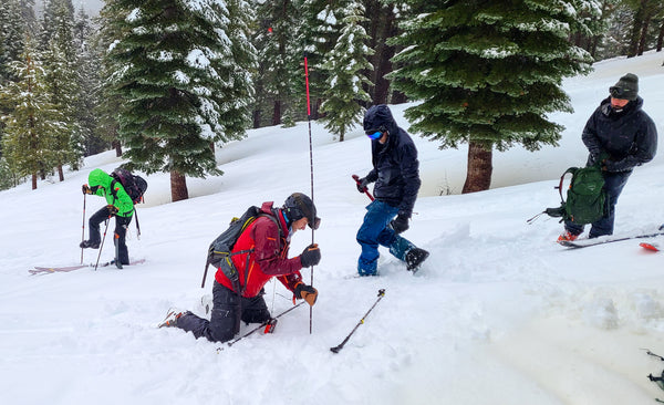 Participants scramble to pinpoint and recover an avalanche victim during an AIARE rescue course