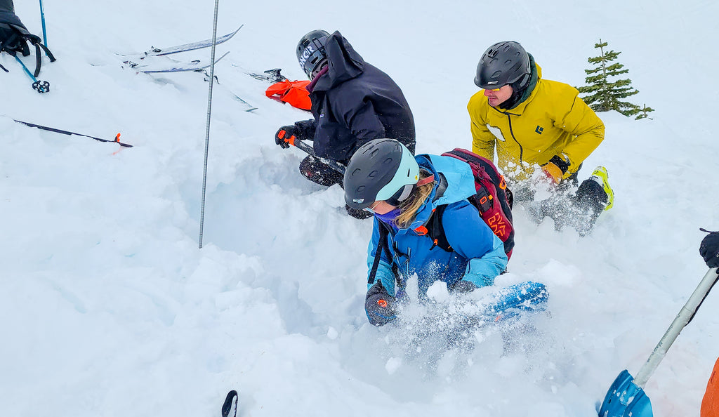 Participants work to uncover an avalanche victim during an AIARE Rescue Course