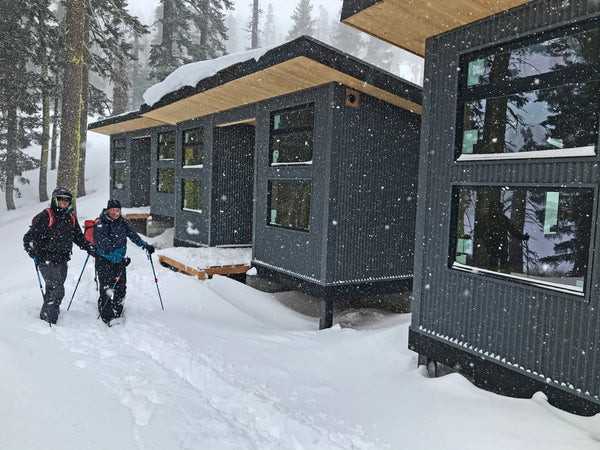Backcountry skiers passing the newly constructed, European style Frog Lake Huts at Frog Lake Cliff in Truckee, California.