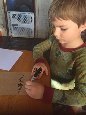 Eli writes thank you notes to SuperGift Capes customers.
