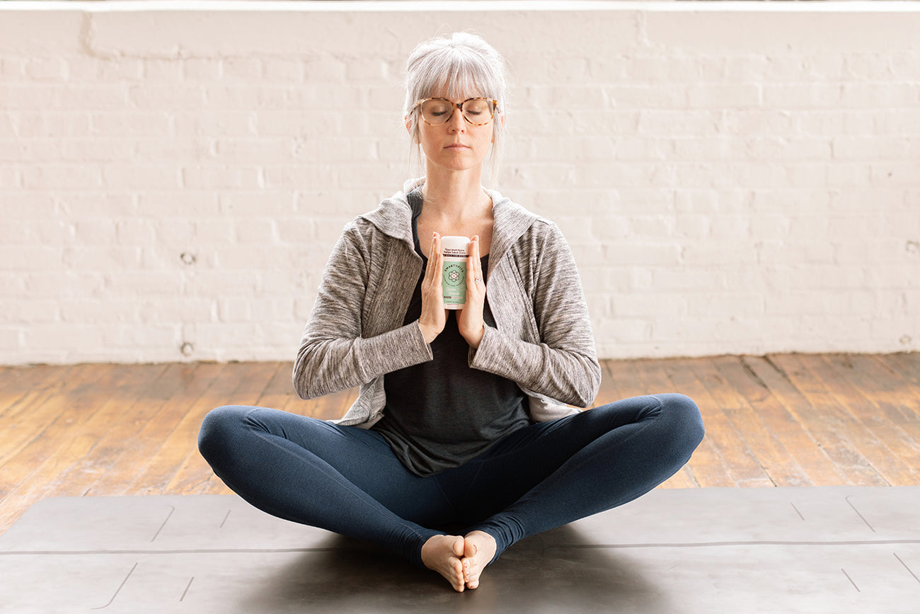 Woman holding smarty pits deodorant in yoga pose