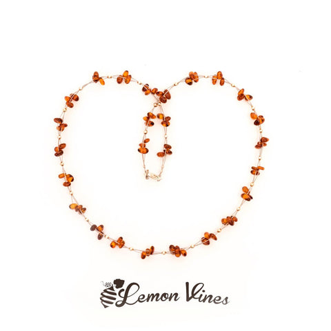 Amber necklace on metal wire. Cognac color