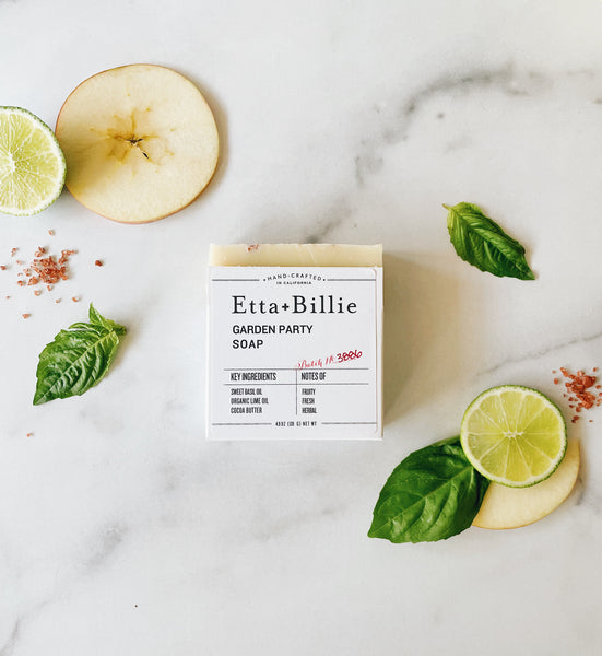 etta and billie new garden party soap flat lay with basil leaves, red lava salt, and apple on marble counter