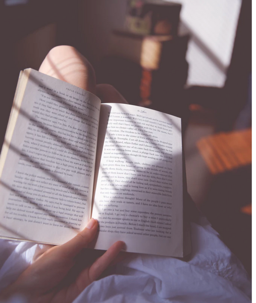 person holding book while lounging in bed