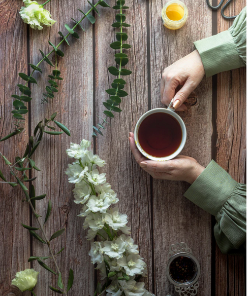 person holding cup of tea with flowers on the table
