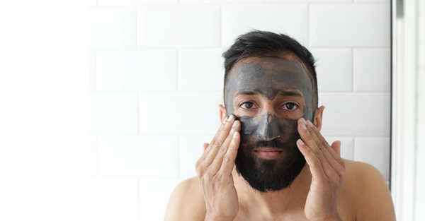 man washes clay exfoliating face mask off his face