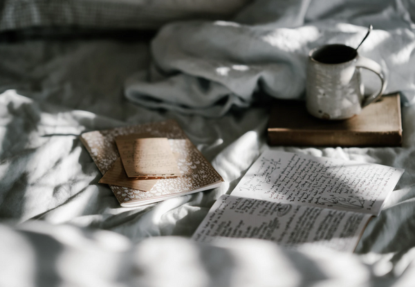 book, coffee, and notes lay on comforter as light shines through the shades