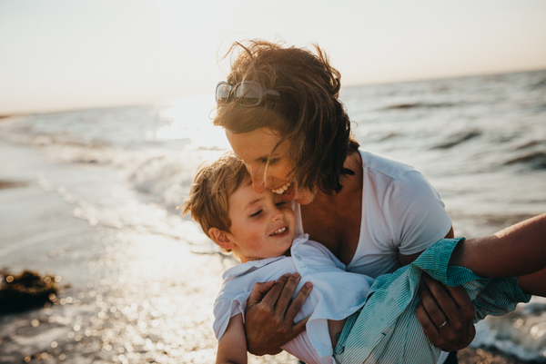 mother and son smiling by the beach