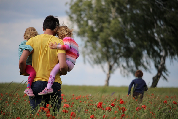 father with 3 kids walks through the grass