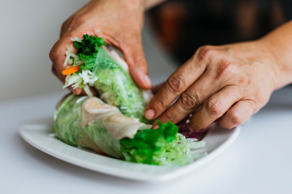 person holding fresh spring rolls over plate