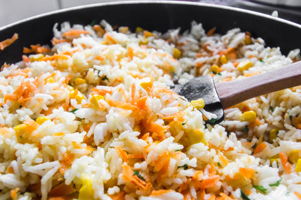 close up on spatula stirring a cooking pot of rice with veggies
