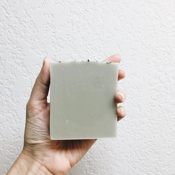 Hand holding up Etta and Biliie soap bar