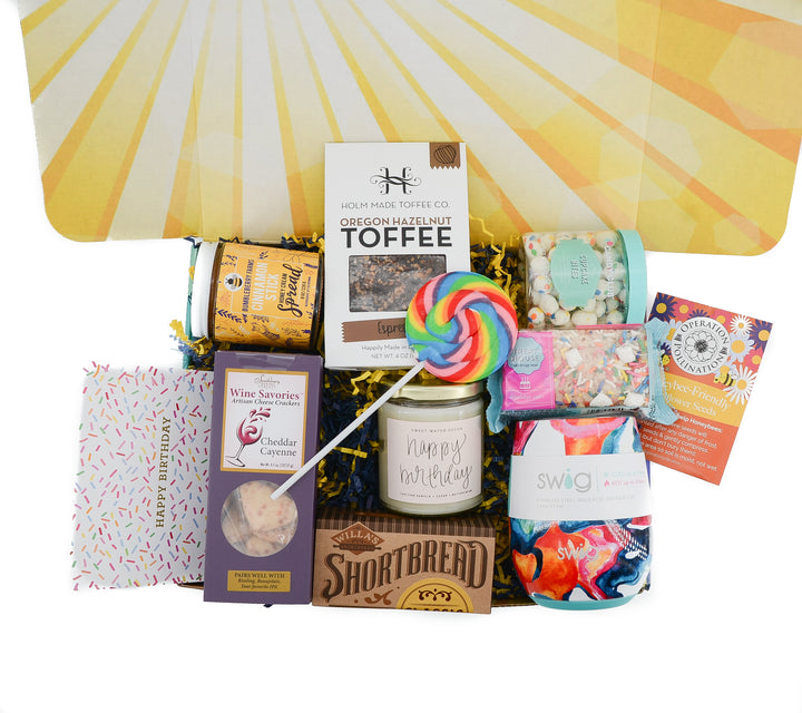 This birthday Gift Box is packed full of goodies and treats! Swig wine tumbler, Toffee, Honey Spread, Wine Crackers, Cookies, Happy Birthday Candle, Cupcake Bites, Birthday Cake Treat, Birthday Card, Lollipop and always our honeybee seeds