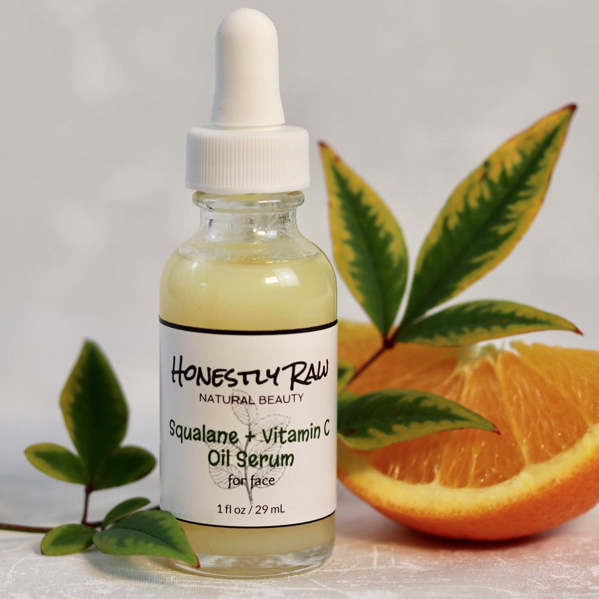 Squalane Vitamin C Oil Serum with leaves and orange slice