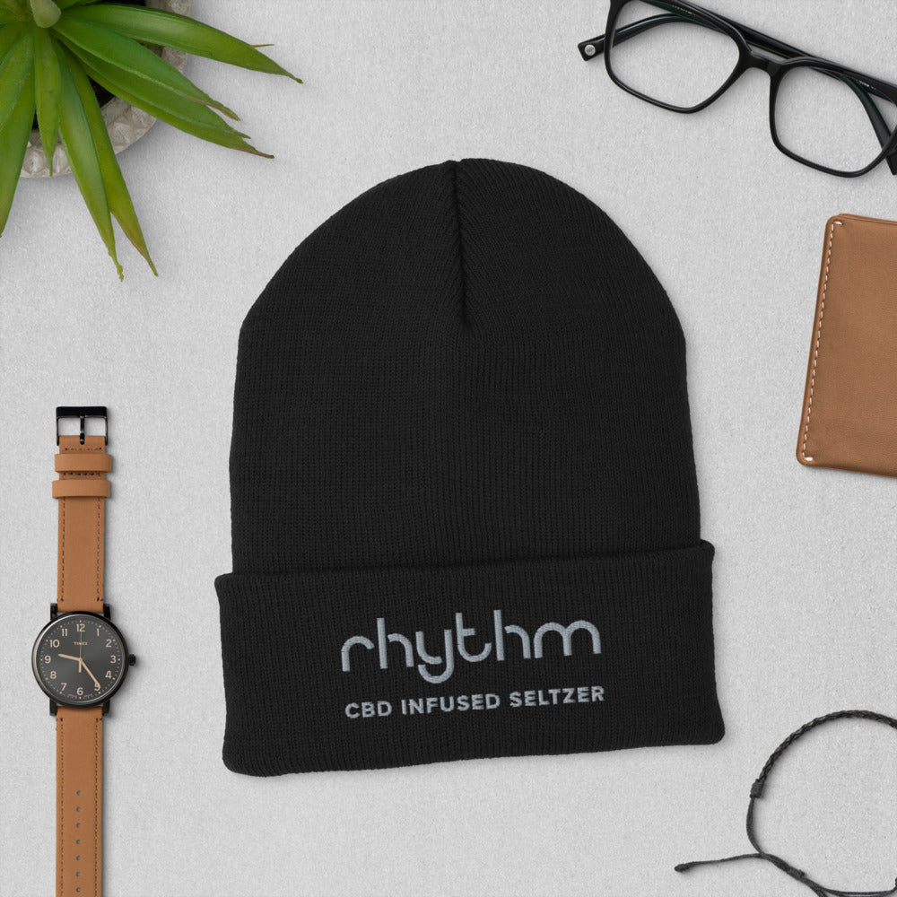 Front view of Rhythm CBD Seltzer cuffed black cuffed beanie with other assorted desk items
