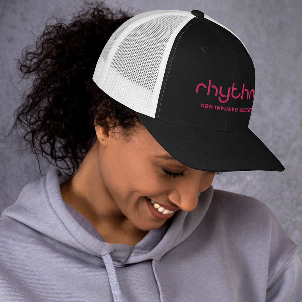 Woman with white Rhythm hat pink logo