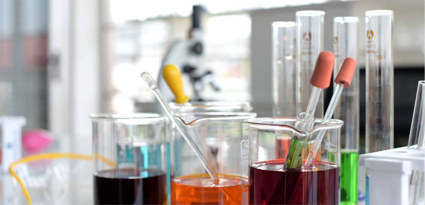 Beakers and test tubes in a laboratory with different colored fluids, droppers and pipettes