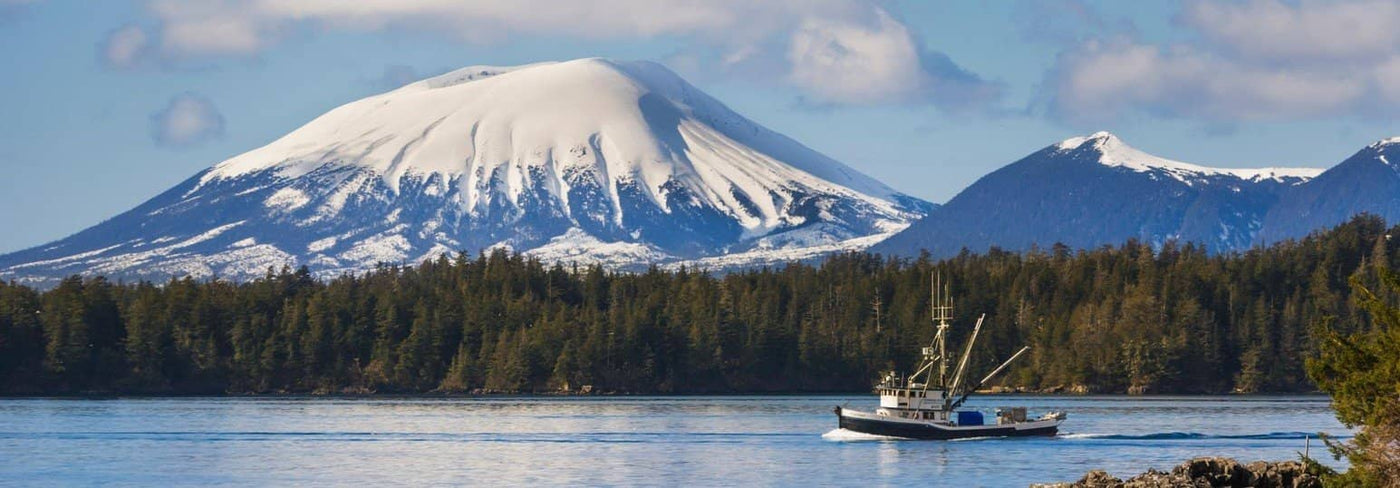 A fishing boat trawling Sitka Sound in Alaskan waters with snow capped mountains in the background
