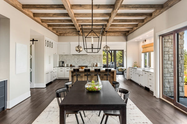 spacious-kitchen-with-large-table-island-and-dark-hardwood-floors-and-white-cabinets-featuring-brass-pulls-by-doorcorner