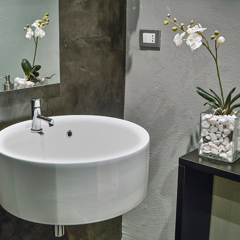 Spa bathroom with white sink and white orchid flower