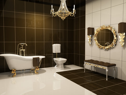Gold and black bathroom with gold mirror and a gold claw foot soaking tub