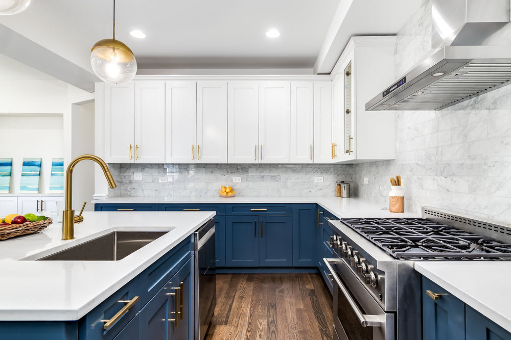 White kitchen with some blue cabinets and brushed brass cabinet pulls