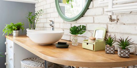 Bathroom counter with a white bowl sink, wood countertop and lots of plants