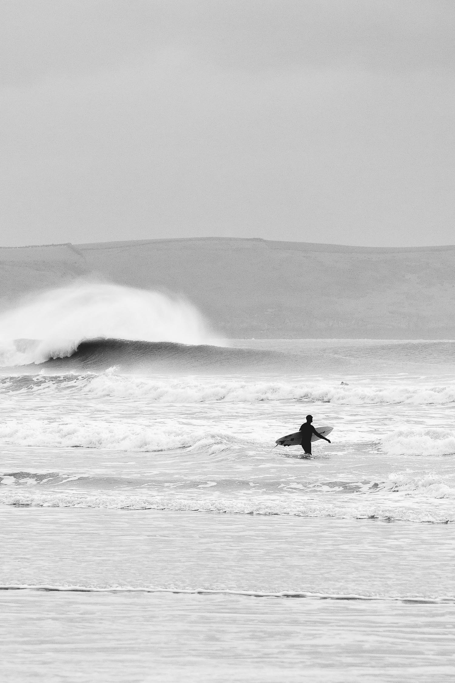 surfer walking out to surf