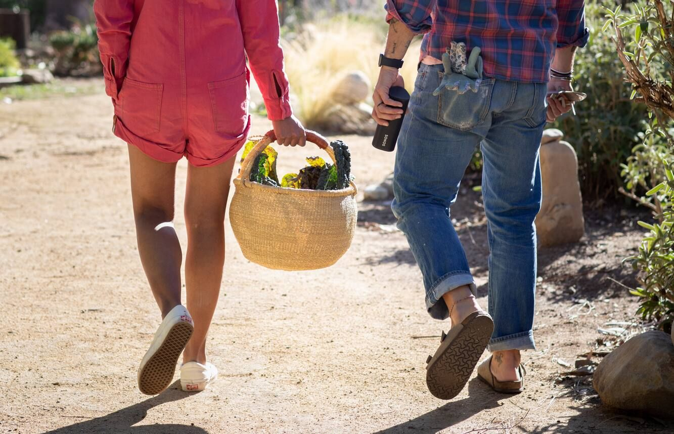 Lady carrying picnic basket and man carrying Sonos Roam