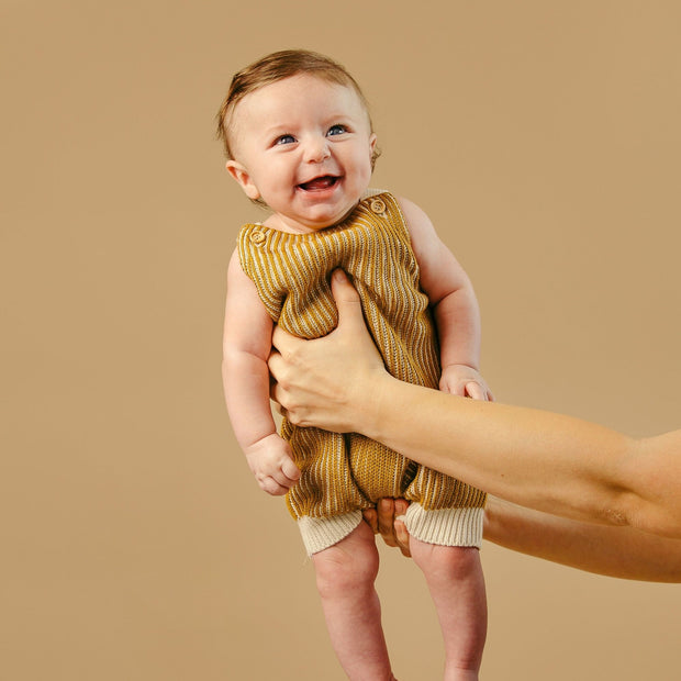 Cutest baby alive smiles while wearing a knit romper in Asheville, North Carolina.