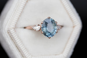 Oval blue green umba sapphire three stone ring, pear side stones