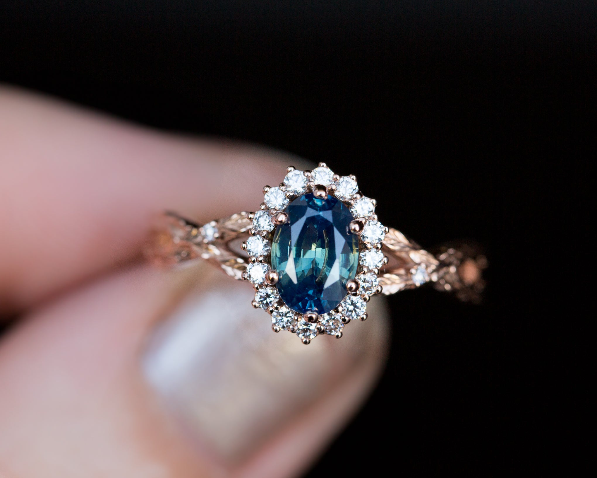Oval halo twisted leaf sapphire ring