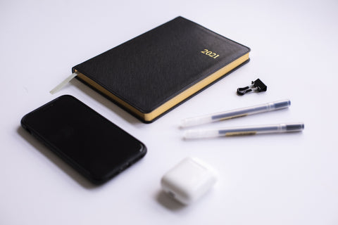 layout of essential stuff - journal, pen, earbuds, phone