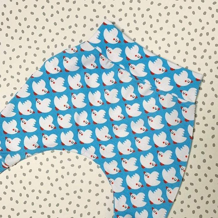 flatlay of baby harem pants in a scandi bird print with rows of white birds with orange beaks flying left and right in alternating rows