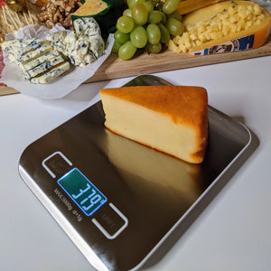 Digital Cheese and Food Scale with Cheese being Weighed - Lavish Cheese