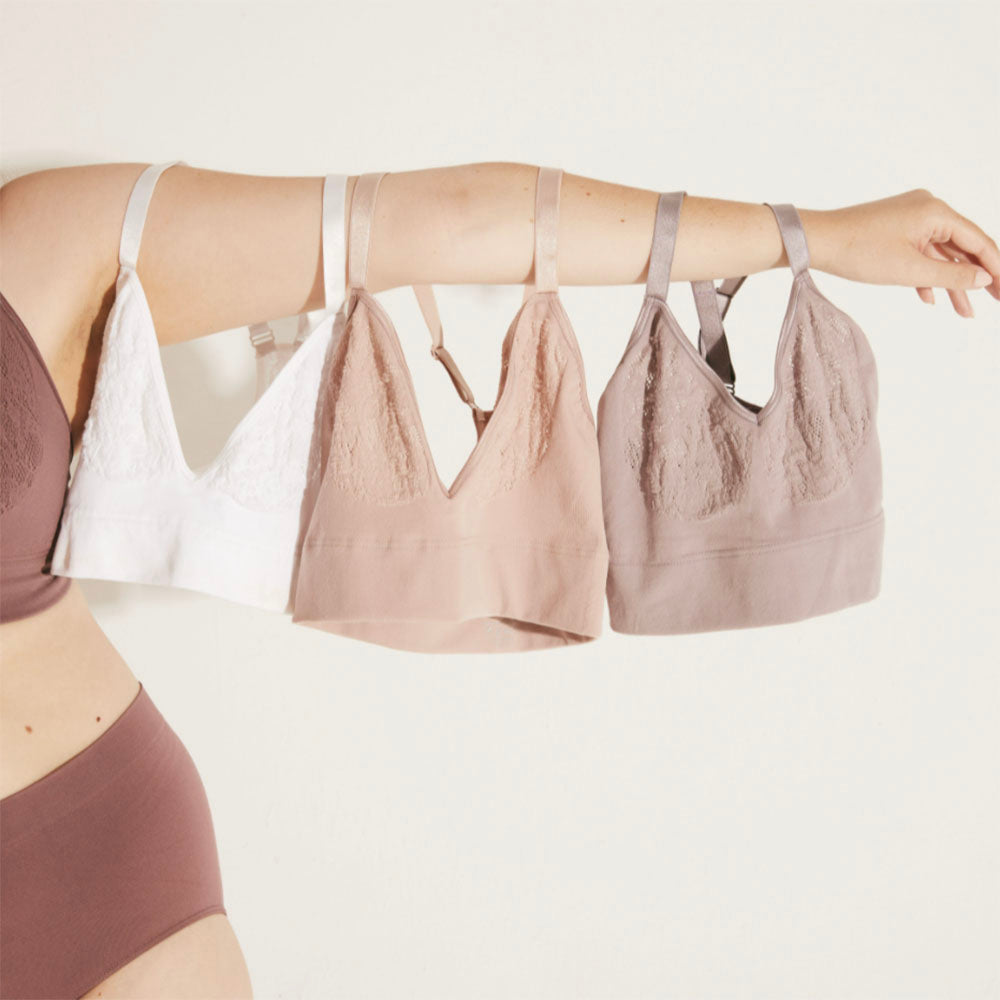 A row of MINDD bras hang from a woman's outstretched arm