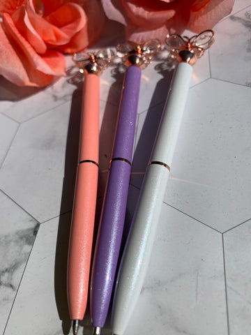 3 ballpoint pens with butterfly toppers. They are pink, purple and white in color.