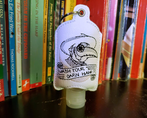 A vinyl hand santizer holder with the plague doctor and Wash Your Darn Hands!