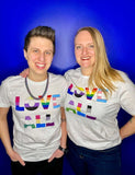 LP with their wife standing in front of a blue background - both are wearing white Dash of Pride LOVE ALL tees