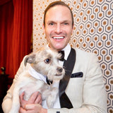 Jason Mitchell Kahn holding his dog wearing a white tuxedo top with black trim.