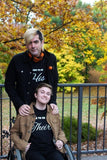 Ross standing behind Logan at the park with fall trees in the background.