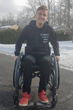 Logan in his wheelchair outside with snow in the background.