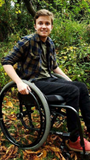 Logan in his wheelchair outside at the park with leaves on the ground.