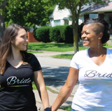 A white woman (L) holding the hand of a black womxn (R) - both wearing Bride shirts with rainbow line